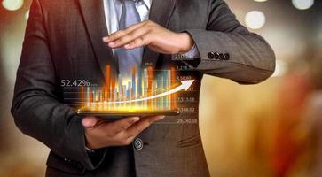 les hommes d'affaires tiennent une tablette, un plan et une stratégie et affichent des hologrammes virtuels de statistiques, de graphiques financiers, de titres et de graphiques sur fond sombre. le concept de croissance de l'entreprise photo