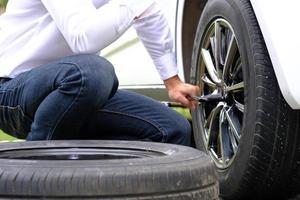 jeune homme asiatique assis sur une voiture cassée appelant à l'aide et réparé des véhicules à roues sur la route, remplaçant les pneus d'hiver et d'été. concept de remplacement des pneus saisonniers photo