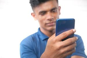 Jeune homme part à l'aide de smart phone isolated on white photo