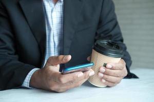 main d'homme d'affaires utilisant un téléphone intelligent et une tasse de café en papier photo