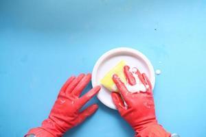 éponge, gants en caoutchouc et plaque colorée sur bleu photo