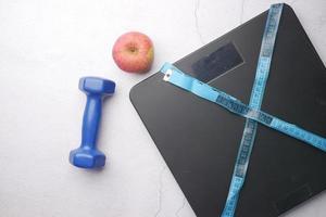 un ruban à mesurer et un pèse-personne sur plancher en bois. photo