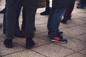 les jambes des hommes avec des chaussures debout sur le trottoir photo