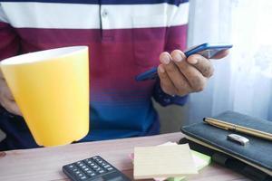 gros plan de la main du jeune homme à l'aide d'un smartphone photo