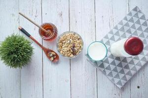 Petit déjeuner de céréales dans un bol avec du pain et du miel sur fond blanc photo