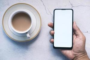 gros plan sur la main du jeune homme à l'aide d'un smartphone avec écran vide photo