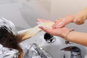 laver la teinture pour les cheveux chez un coiffeur, retirer le papier d'aluminium des cheveux. photo