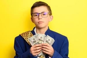 un garçon à lunettes et un costume surdimensionné avec un visage satisfait nous tient des dollars, un enfant et beaucoup d'argent. photo