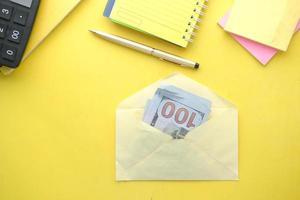 gros plan de l'argent en dollars américains dans une enveloppe sur fond jaune photo