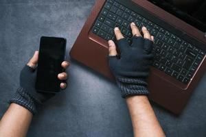 main de pirate volant des données d'un ordinateur portable, vue de haut en bas photo