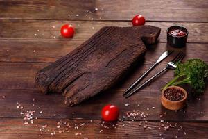 planche à découper en bois ainsi que des légumes et une table sombre spéciale photo