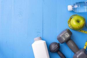 équipement de fitness et aliments santé sur fond de bois bleu photo