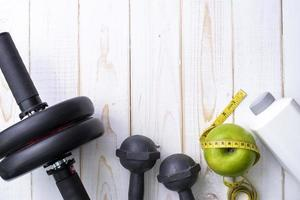 équipement de fitness et aliments santé sur fond de bois blanc photo