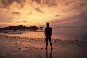 un homme réfléchi sur la plage au coucher du soleil photo