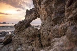 beau rocher sur la plage au coucher du soleil photo