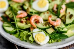salade aux crevettes, avocat, concombre, graines de citrouille et graines de lin à l'huile d'olive photo