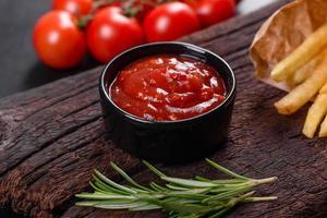 frites fraîches savoureuses et sauce rouge sur une planche à découper en bois photo