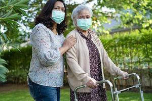 Une vieille dame asiatique âgée ou âgée marche avec un marcheur et porte un masque facial pour protéger l'infection de sécurité par le coronavirus covid-19. photo