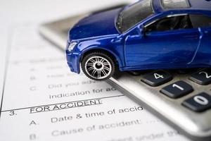 voiture sur fond de formulaire d'accident de voiture d'assurance, prêt de voiture, finance, économies d'argent, assurance et concepts de temps de location. photo
