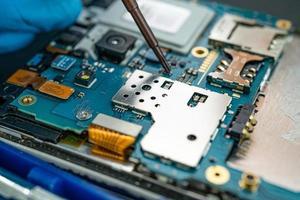 technicien réparant l'intérieur du téléphone portable en fer à souder. circuit intégré. le concept de données, de matériel, de technologie. photo