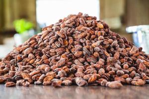 fèves de cacao crues sur une table en bois photo