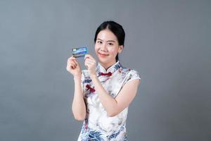 une femme asiatique porte une robe traditionnelle chinoise avec une main tenant une carte de crédit photo