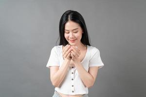 jeune femme asiatique avec un visage heureux et une main tenant une tasse de café photo
