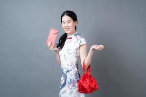 une femme asiatique porte une robe traditionnelle chinoise avec une enveloppe rouge ou un paquet rouge photo