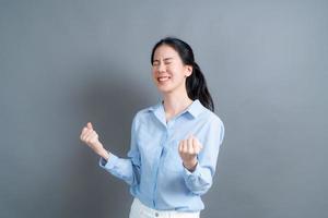femme asiatique se réjouissant de son succès et de sa victoire en serrant les poings de joie. femme chanceuse étant heureuse d'atteindre son but et ses objectifs. émotions positives, sentiments. photo