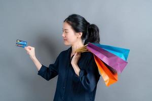 belle femme asiatique avec des sacs à provisions et montrant une carte de crédit photo