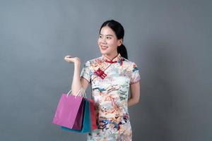 une femme asiatique porte une robe traditionnelle chinoise avec une main tenant un sac à provisions photo