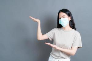 une femme asiatique portant un masque médical protège la poussière du filtre pm2.5 anti-pollution, anti-smog et covid-19 avec présentation à la main photo