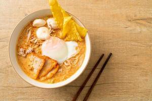 nouilles de vermicelles de riz avec boulette de viande, porc rôti et œuf dans une soupe épicée photo