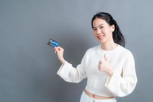 portrait d'une jolie jeune femme asiatique en pull montrant une carte de crédit avec espace de copie photo