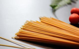 spaghettis longs jaunes sur fond noir. pâtes fines disposées en rangées. pâtes italiennes jaunes. spaghettis crus à la bolognaise. papier peint spaghetti cru. spaghettis fins. concept de fond de nourriture. photo