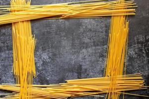 longs spaghettis jaunes sur fond rustique. pâtes italiennes jaunes. longs spaghettis. spaghettis crus à la bolognaise. spaghettis crus. concept de fond de nourriture. concept de cuisine et de menu italien. photo