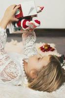 jolie petite fille allongée sur le sol, jouant avec la décoration de noël, petit père noël sortant de la boîte photo