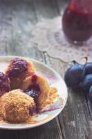 boulettes de prunes, prunes et sauce aux prunes sur fond de bois photo