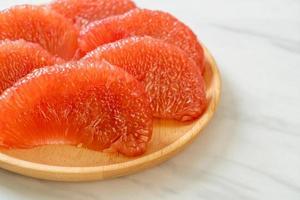 Pomelo rouge frais ou pamplemousse sur assiette photo