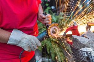 homme serrurier utilisant une scie pour couper un morceau de fer à l'extérieur. photo