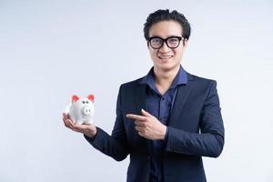 portrait d'un homme d'affaires asiatique tenant une tirelire photo