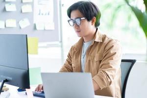 homme d'affaires asiatique travaillant avec un ordinateur portable au bureau photo