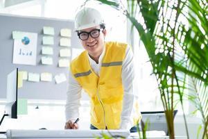 les ingénieurs asiatiques font des dessins de construction photo