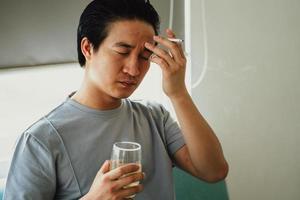 l'homme asiatique se sent désespéré pour la dépendance au tabac photo