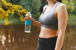 photo en gros plan d'une femme sportive à l'extérieur au coucher du soleil tenant une bouteille d'eau en verre, restez hydraté