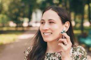 jeune femme souriante à l'extérieur dans le parc de la ville à l'aide d'écouteurs et écoutant de la musique ou parlant au téléphone photo