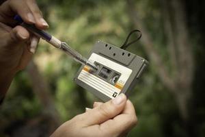 Les femmes rembobinent une cassette compacte vintage sur fond flou, gros plan sur un ensemble de vieilles cassettes audio, ret photo