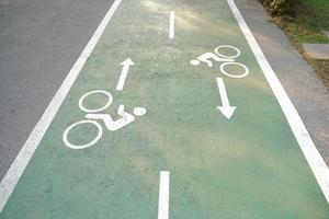 des panneaux de voie cyclable peints sur une voie cyclable verte. piste cyclable dans le parc. photo