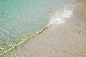 vague et plage de sable blanc. photo
