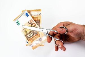 homme coupant des billets de 50 euros avec des ciseaux photo